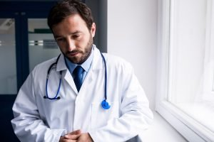 A male doctor looks down sadly