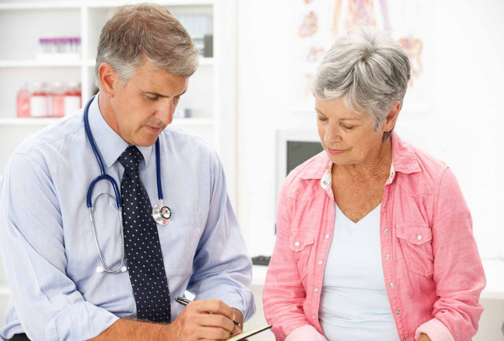 A male doctor consults with a female patient